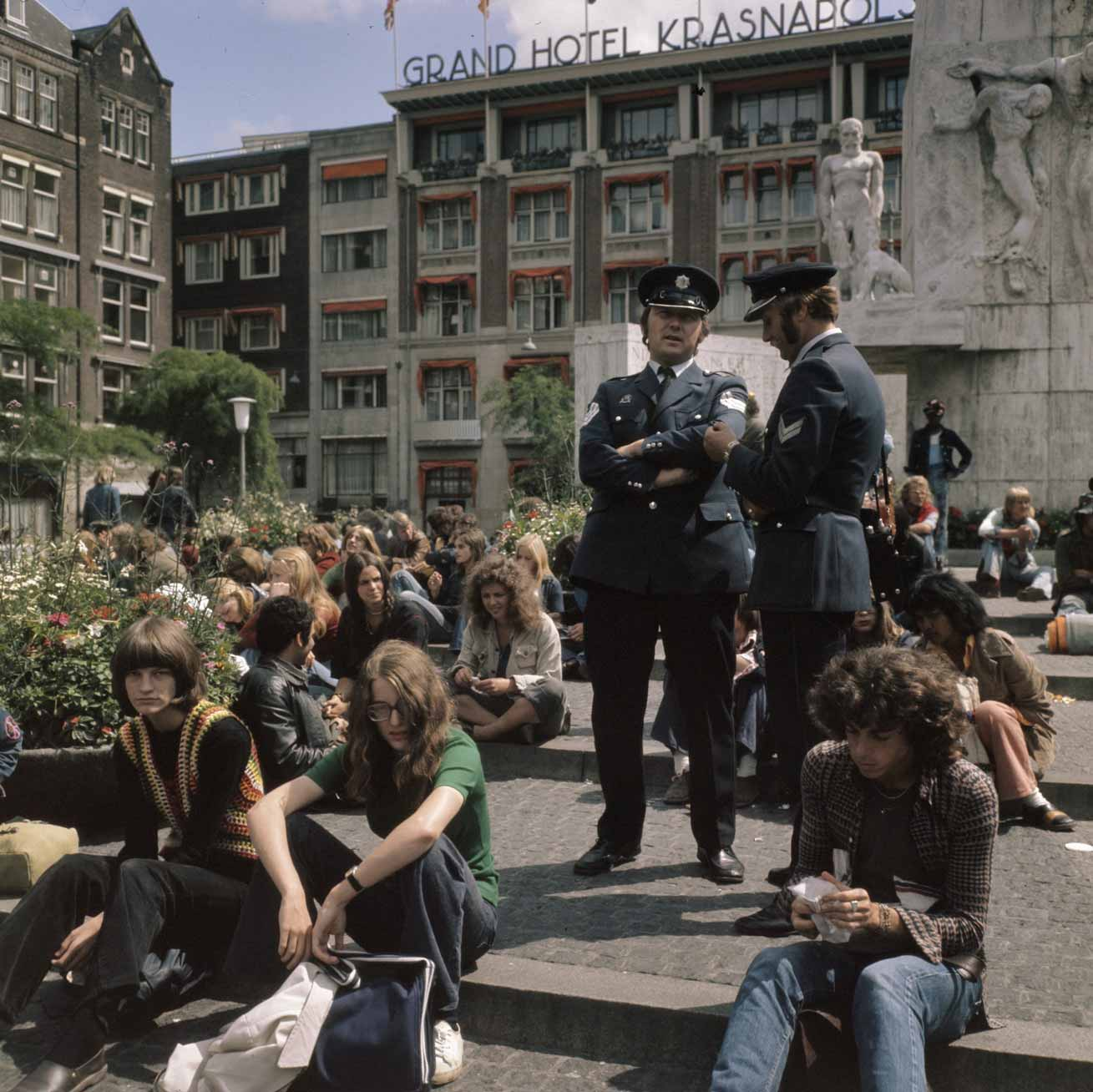 Youth in Amsterdam at Monument on Dam Square in Amsterdam, 1973. <br>Photographer: Bert Verhoeff / Anefo, Courtesy of the National Archives of the Netherlands (Public Domain).